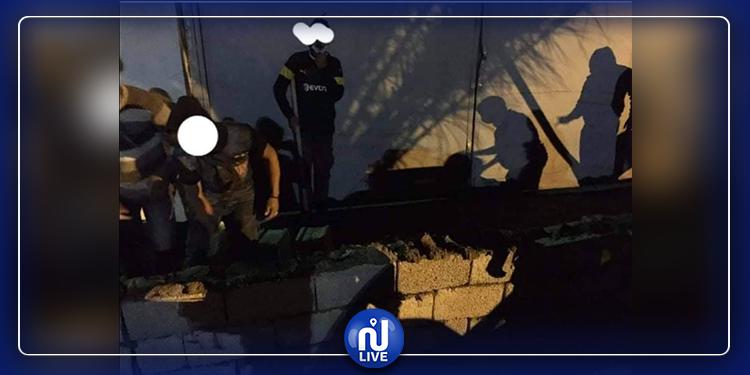 Un mur en béton devant des véhicules libyens en provenance de Tunisie