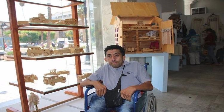 شاب يتحدى إعاقته العضوية ويحوّل الخشب الي تحف فنية (صور)