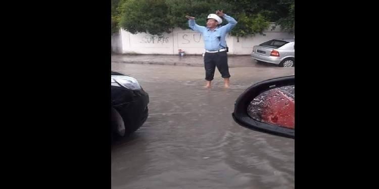 Un agent de la circulation intrépide, sous les trombes d'eau (Photos)